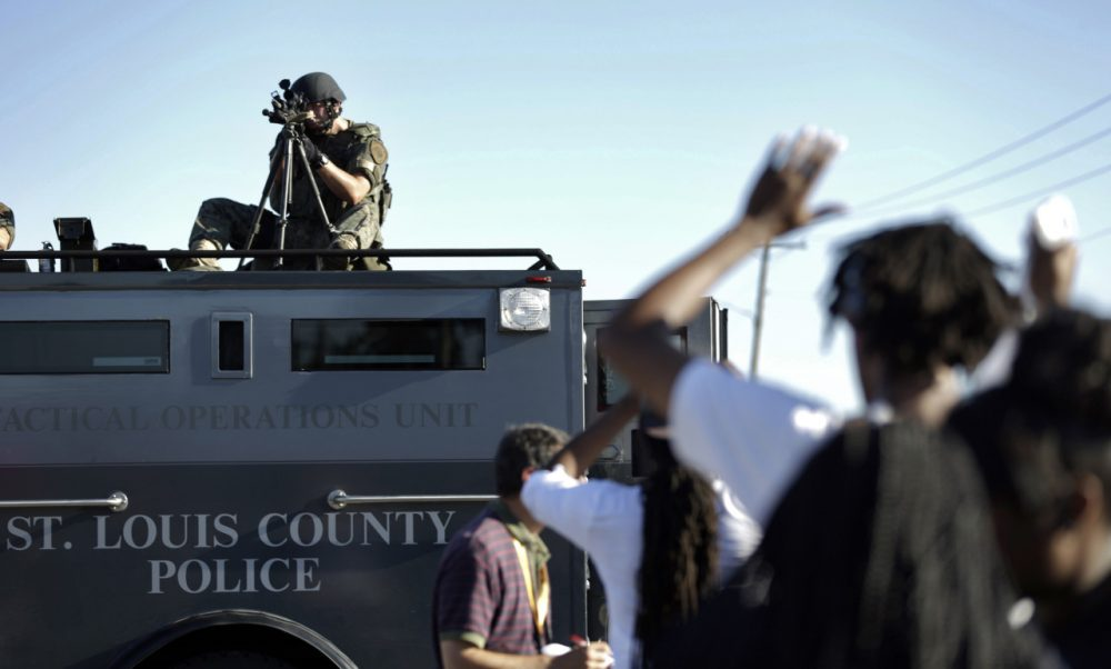 A member of the St. Louis County Police Department points his weapon in the direction of a group of protesters in Ferguson, Mo. on Wednesday, Aug. 13, 2014. On Saturday, Aug. 9, 2014, a white police officer fatally shot Michael Brown, an unarmed black teenager, in the St. Louis suburb. (Jeff Roberson/AP)