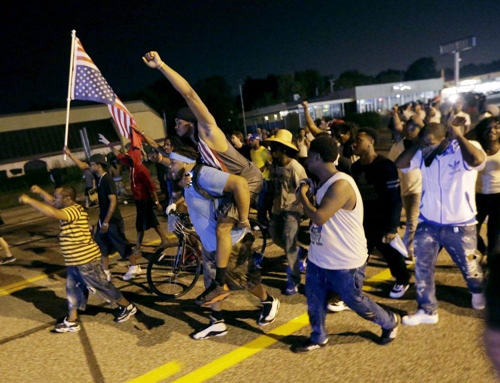 People march down the street after a standoff with police Monday in Ferguson. (Charlie Riedel/AP)