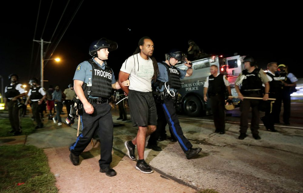 A man is lead away by police during a protest Monday in Ferguson, Mo. (Charlie Riedel/AP)