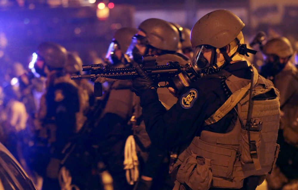 Police advance after tear gas was used to disperse a crowd Sunday, Aug. 17 during a protest for Michael Brown, who was killed by a police officer last Saturday in Ferguson, Mo. (Charlie Riedel/AP)