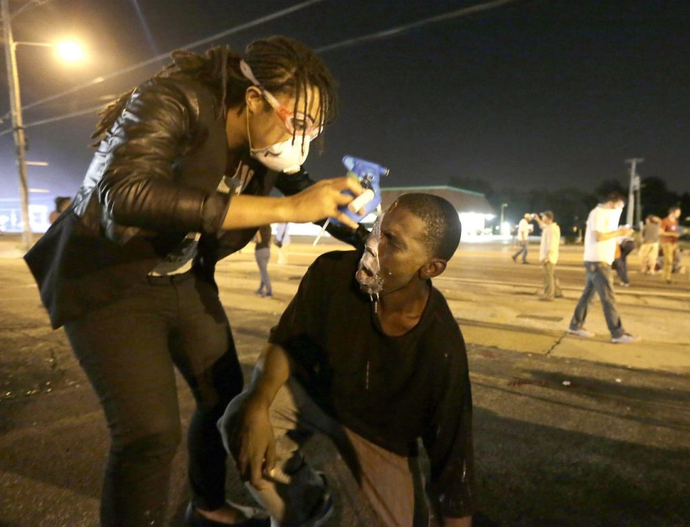 A man is helped ease the effects of tear gas during a protest Monday. (Charlie Riedel/AP)