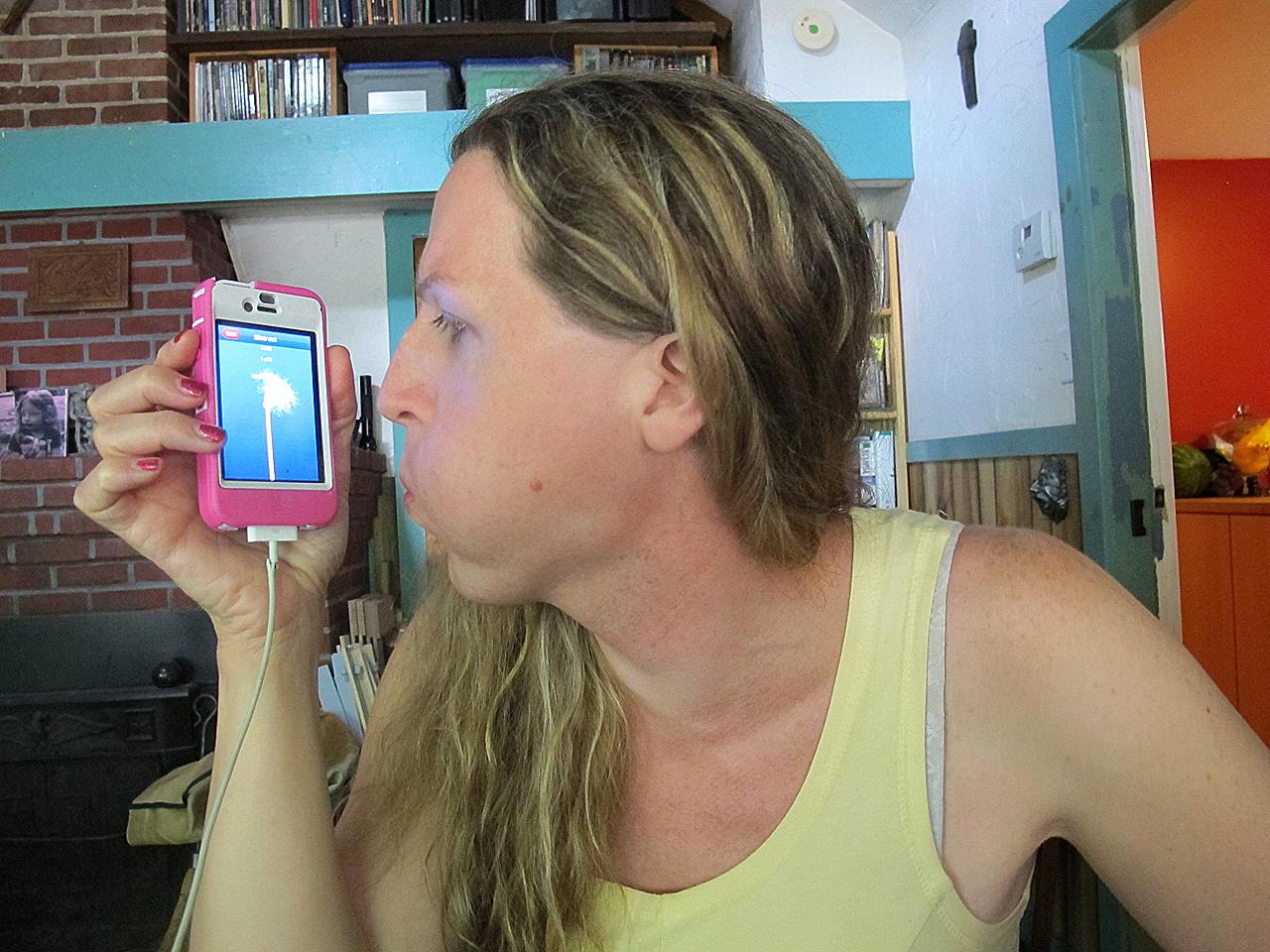 Lorelei Erisis tries out the Eva app in her Ayer home. (Martha Bebinger/WBUR)