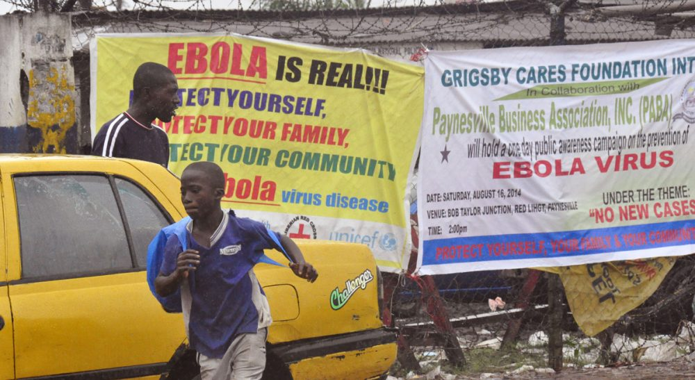 """Catherine Womack: """"In health care, we're always looking for a magic pill or new technology to save us. But in this case, the focus on experimental drugs -- who gets them, how much there is of them, when will there be more -- is a distraction from what the Ebola-stricken countries really need."""" Pictured: People pass by Ebola virus health warning signs, in the city of Monrovia, Liberia, Sunday, August 17, 2014. (Abbas Dulleh/AP)"""