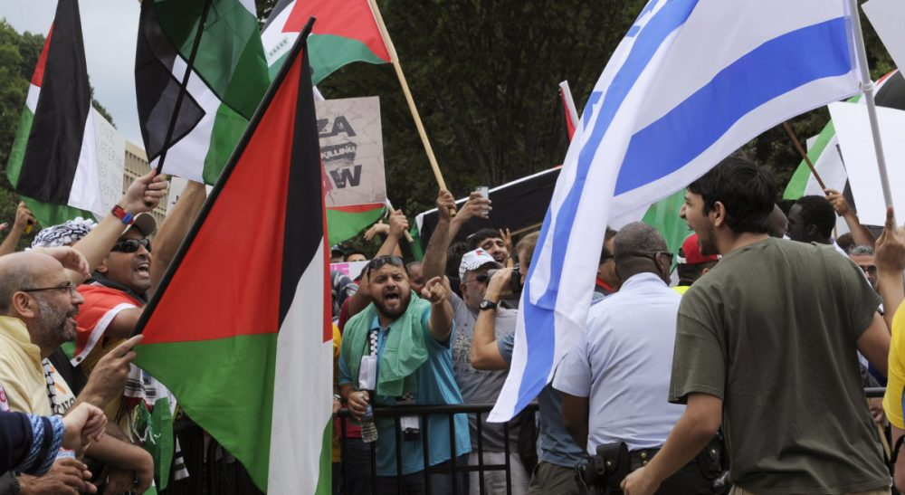 """Noam Waksman: """"If Hani and I had grown up in Palestine and Israel respectively, the boundaries between us would have been numerous, institutional, and tangible."""" Pictured: An Israeli supporter shouts at right, as Palestinian supporters shout at, left, during a rally near the White House in Washington, Saturday, Aug. 2, 2014. (Susan Walsh/AP)"""