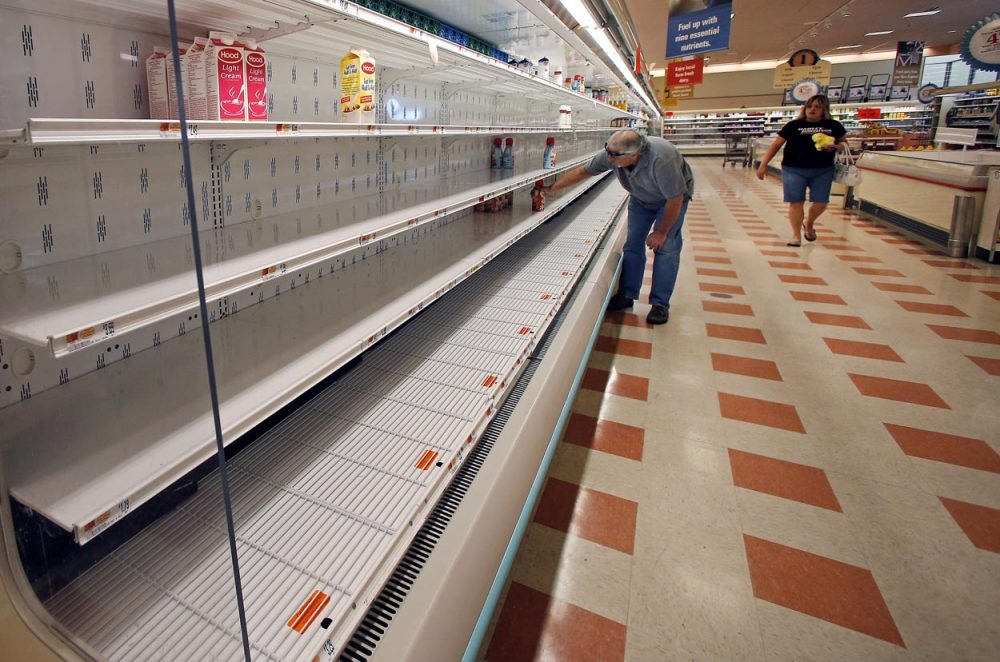 A shopper reaches into a mostly empty dairy shelf at Market Basket in Haverhill on Monday. (Elise Amendola/AP)