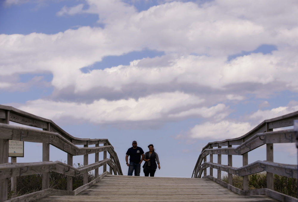 Two people walk across a beach bridge in the warmth of a spring afternoon on Duxbury Beach in May 2014 in Duxbury, Mass. (Stephan Savoia/AP)