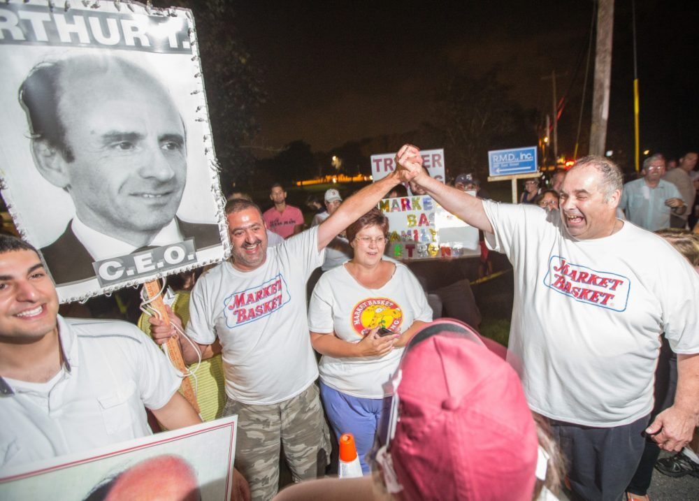 Protesters celebrate outside Market Basket headquarters in Tewksbury last Wednesday night after the grocery chain reached a deal to return control back to Arthur T. Demoulas. (Aram Boghosian for WBUR