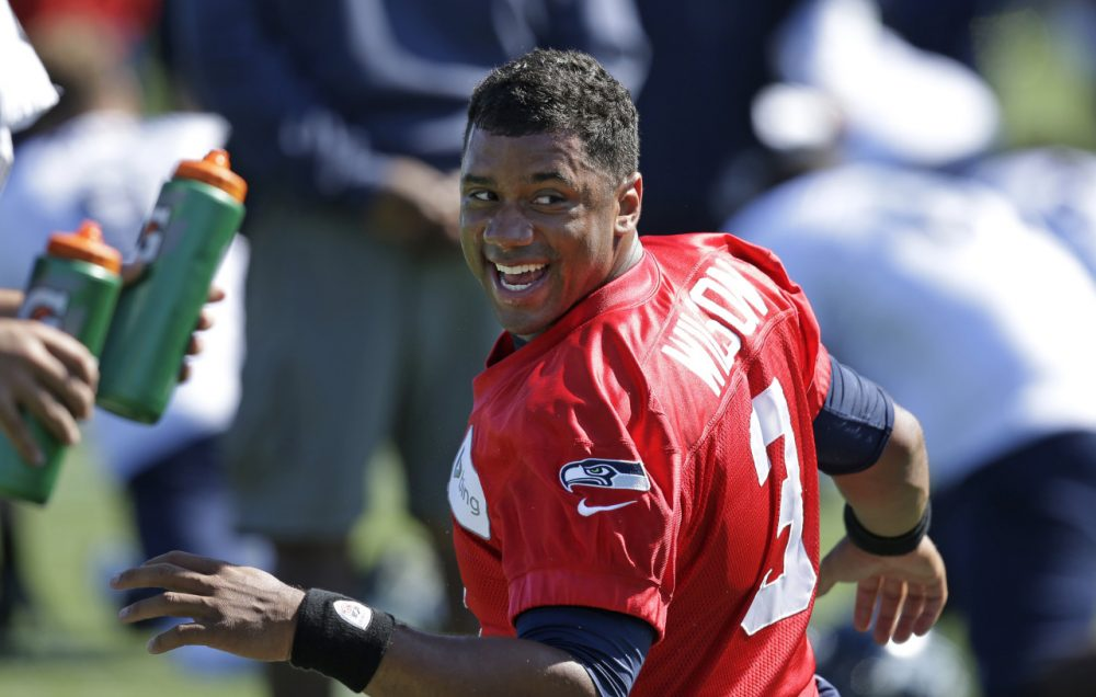 Russell Wilson and the Seattle Seahawks open the 2014 NFL season Thursday against the Green Bay Packers. (Elaine Thompson/AP Images)