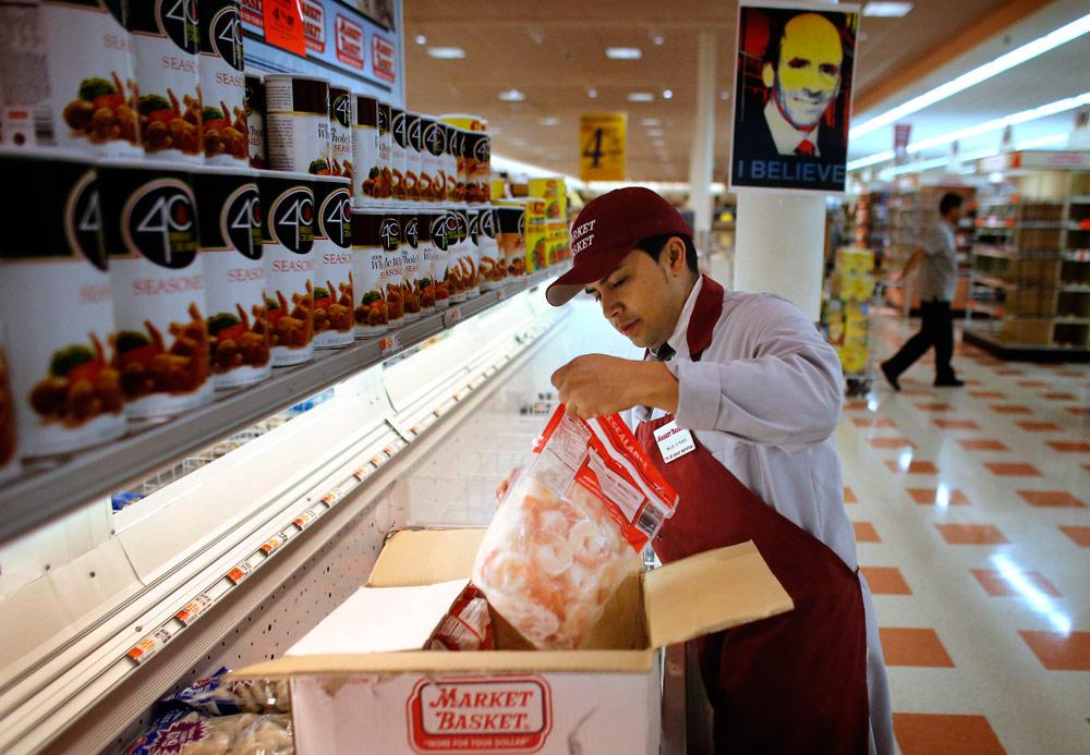Market Basket employee Melbi Peraza, of Chelsea, restocks frozen shrimp at a Market Basket location in Chelsea Thursday. (Steven Senne/AP)
