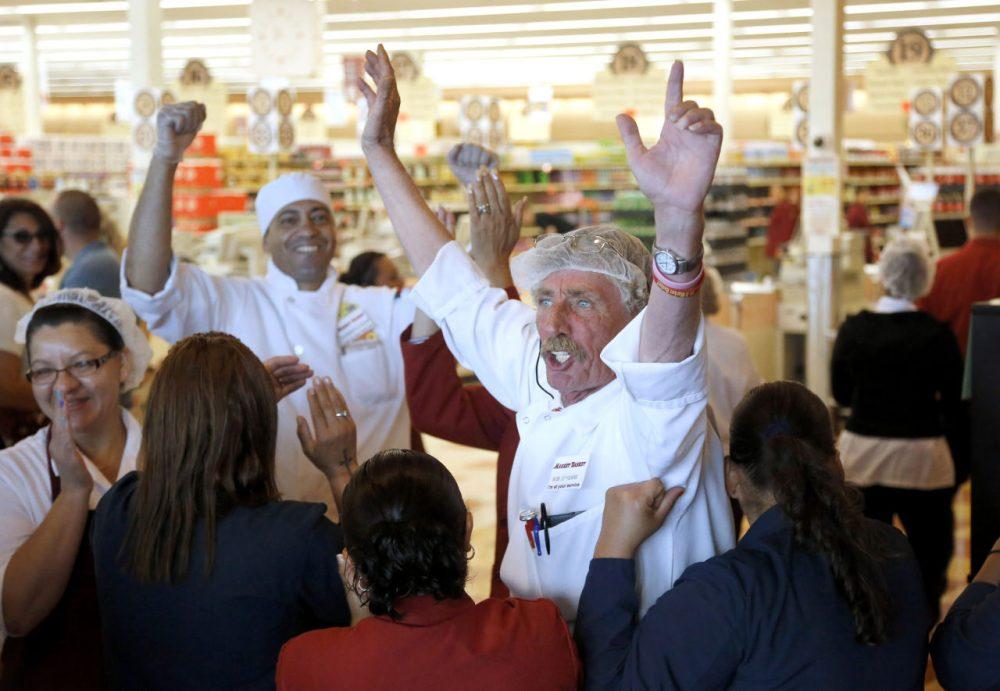 Market Basket meat manager Bob Dietz, of Methuen, Mass., center, raises his arms in celebration after watching a televised speech by restored Market Basket CEO Arthur T. Demoulas Thursday. (Steven Senne/AP)