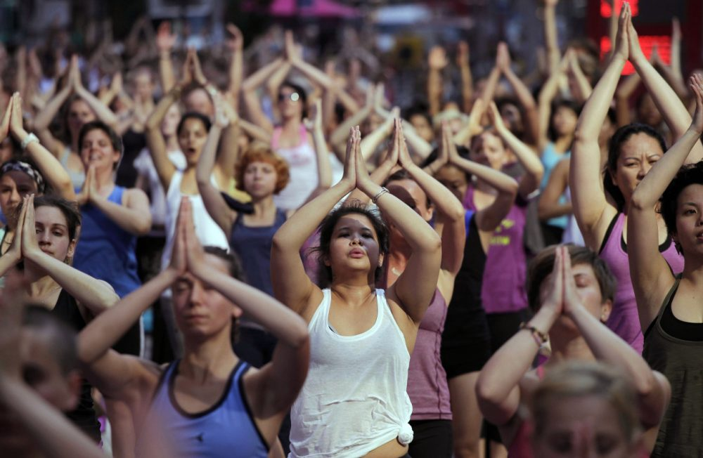 "Anita Diamant: ""His approach -- making yoga accessible to everybody -- is not sweaty or sexy. Which isn't to say that it's easy."" Pictured: Thousands of yoga enthusiasts convene in New York's Times Square to mark the summer solstice, Wednesday, June 20, 2012. (Mark Lennihan/AP)"