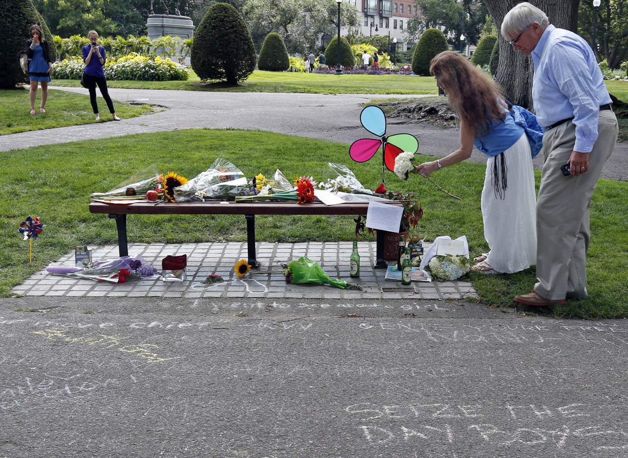 """Don Makson watches as Suzette Demarais places flowers on a bench at Boston's Public Garden, Tuesday, Aug. 12, 2014, where a small memorial has sprung up at the place where Robin Williams filmed a scene during the movie, """"Good Will Hunting."""" Williams, 63, died at his San Francisco Bay Area home Monday in an apparent suicide. (AP)"""