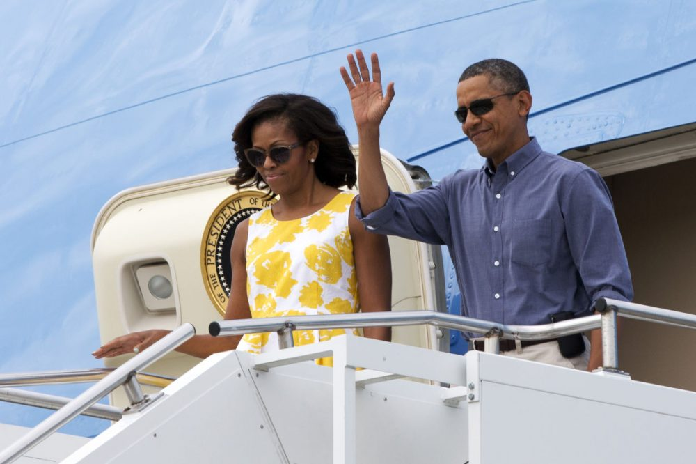 President Barack Obama and first lady Michelle Obama wave as they arrive in Cape Cod, Mass., to fly via helicopter to begin their family vacation in Martha's Vineyard in August 2013.  (Jacquelyn Martin/AP)