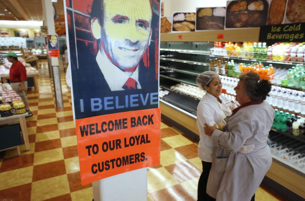 Market Basket employees Cristhian Romero, of Chelsea, Mass., second from right, and Tracie Parker, of Lynn, Mass., right, embrace near a likeness of Arthur T. Demoulas, top, at a Market Basket supermarket location, Thursday, Aug. 28, 2014, in Chelsea. A six-week standoff between thousands of employees of the New England supermarket chain and management has ended with the news that beloved former CEO Demoulas is back in control after buying the entire company. (AP)