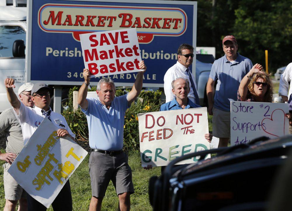 Protesters hold signs and taunt a car entering the site of a Market Basket Supermarket job fair in Andover, Mass., Wednesday, Aug. 6, 2014. Market Basket employees and their supporters are calling for the reinstatement of their fired CEO, even as the company is in the midst of a three-day job fair to replace employees who have refused to work during a revolt that is costing the supermarket chain millions. (AP)