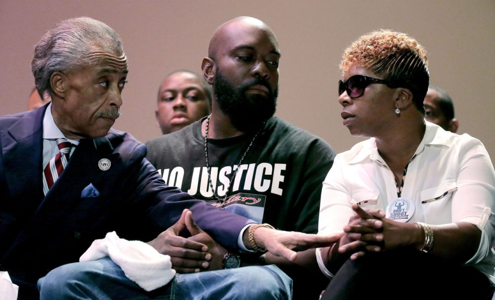 "Rev. Al Sharpton, left, speaks with parents of Michael Brown, Michael Brown Sr. and Lesley McSpadden, right, during a rally at Greater Grace Church, Sunday, Aug. 17, 2014, for their son who was killed by police last Saturday in Ferguson, Mo. Sharpton told the rally Brown's death was a ""defining moment for this country."" (AP)"