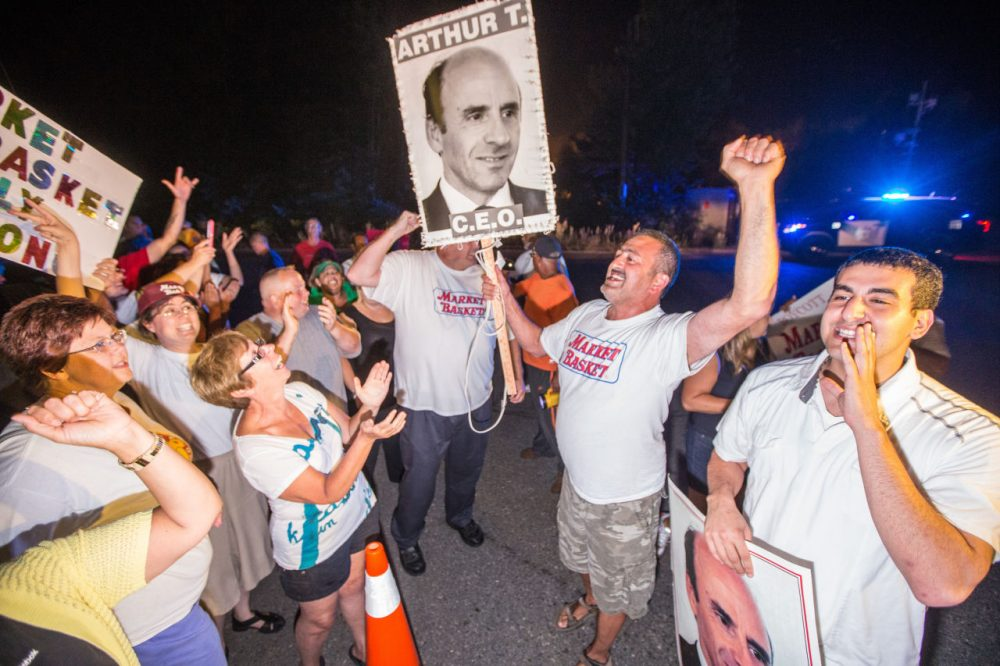 Protesters celebrate outside Market Basket headquarters in Tewksbury after the grocery chain reached a deal to return control back to Arthur T. Demoulas. (Aram Boghosian for WBUR)