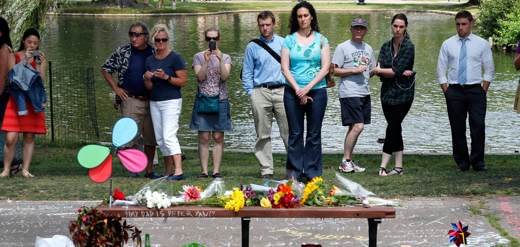 "People pause by a bench at Boston's Public Garden Tuesday, where a small memorial has sprung up at the place where Robin Williams filmed a scene during the film ""Good Will Hunting."" Williams, 63, died at his San Francisco Bay Area home Monday in an apparent suicide. (Elise Amendola/AP)"