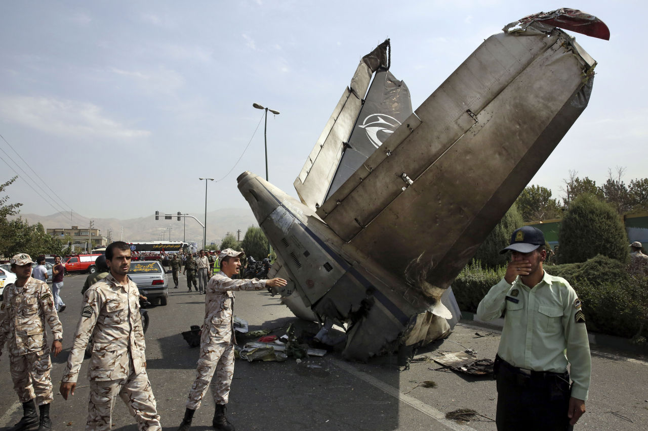Iranian Revolutionary Guards and police officers inspect the site of a passenger plane crash near the capital Tehran, Iran, Sunday, Aug. 10, 2014. An Iranian passenger plane crashed Sunday while taking off from an airport near the capital, killing tens of people onboard, state media reported. (Vahid Salemi/AP)