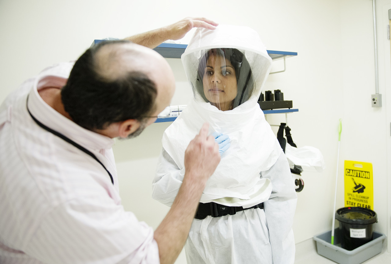 Dr. Nahid Bhadelia in protective gear with Dr. Guillermo Madico at the National Emerging Infectious Diseases Laboratory in Boston, where she directs infection control. This gear is slated to be donated to the Ebola-fighting efforts in Sierra Leone when she goes there in mid-August. (Photo: Jackie Ricciardi, BU Photo Services)