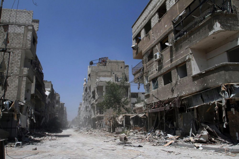 Buildings damaged during battles between Syrian troops and rebels stand along an empty street in Mleiha, some six miles southeast of downtown Damascus, Syria. (AP)