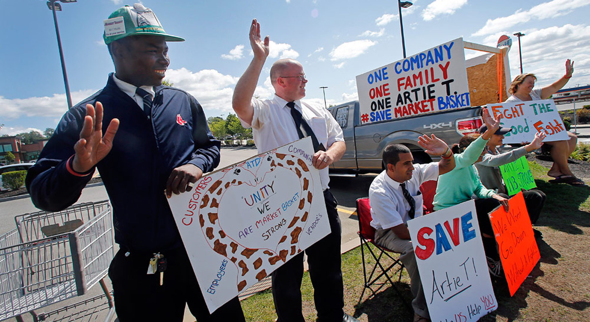 The recent Market Basket dispute demonstrates that America's labor law is in dire need of reform. Pictured: Market Basket employees hold signs and wave to passing supporters outside the supermarket in Haverhill, Mass., Monday, Aug. 18, 2014. (Elise Amendola/AP)