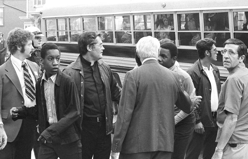 Two black students walk through a line of officials as they leave a bus to attend predominantly white South Boston High School on Sept. 12, 1974, the first day of a court-ordered busing.