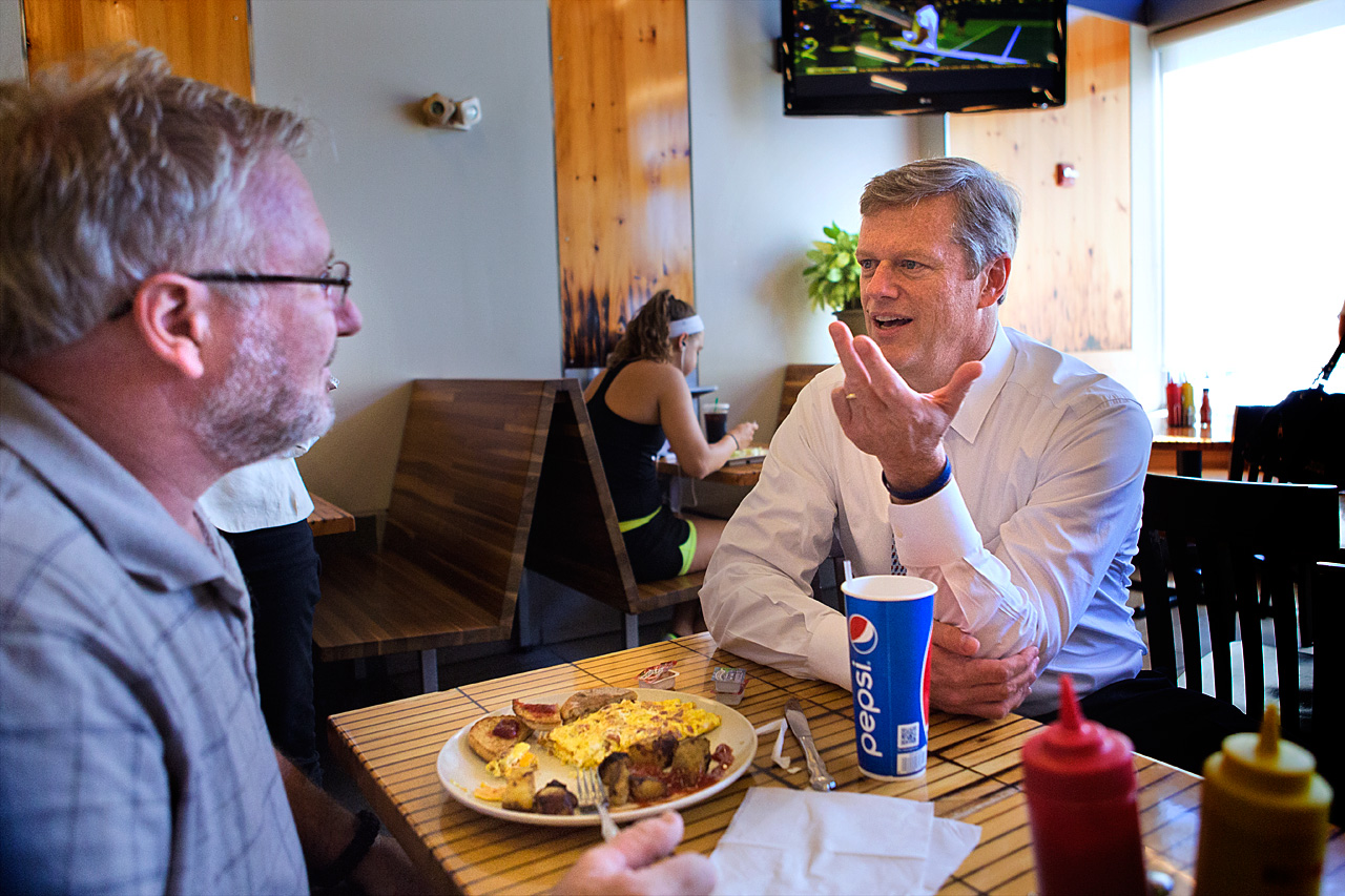 Republican gubernatorial candidate Charlie Baker, right, chats with Bradford Herrick, of Bridgewater, during a visit at Eagle's Deli in Boston. (Jesse Costa/WBUR)