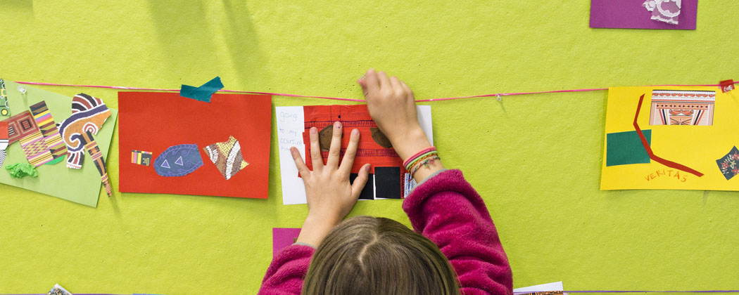 A child hangs art during one of the Museum of Fine Arts, Boston community days. (Courtesy MFA)