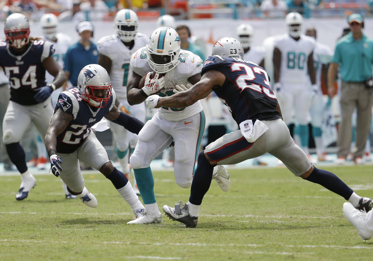 Patriots cornerback Darrelle Revis (24) and  free safety Patrick Chung (23) attempt to tackle Miami Dolphins running back Knowshon Moreno (28) during the second half of an NFL  football game, in Miami Gardens, Fla., Sunday Sept. 7, 2014. (Lynne Sladky/AP)