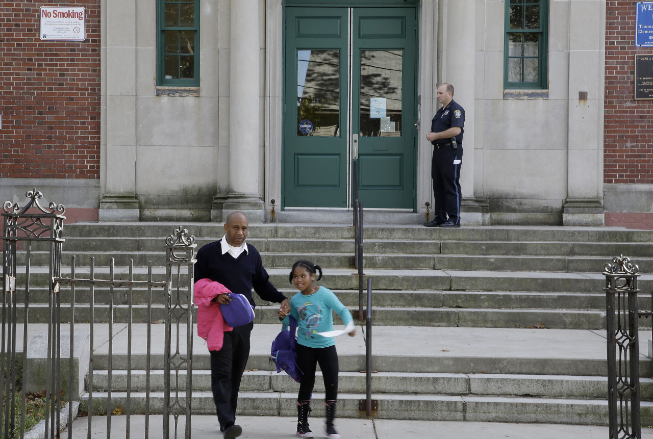 Gairy Bruce walks his daughter Shairy out of the gate at the Thomas J. Kenny Elementary School in Boston. (Stephan Savoia/AP)