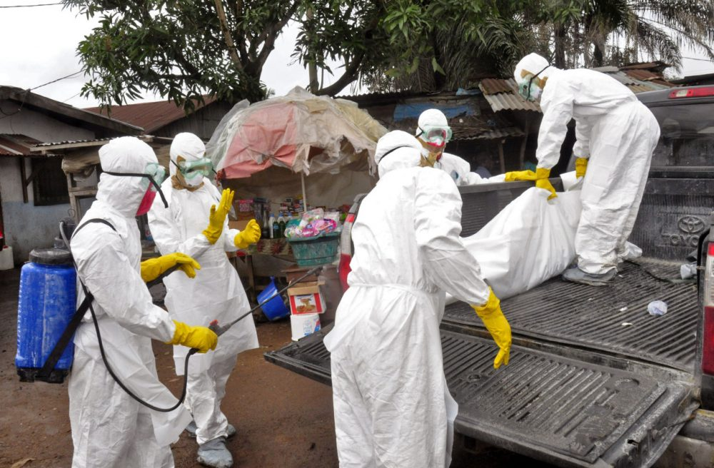 Health workers load the body of a woman they suspect died from the Ebola virus, onto a truck in front of a makeshift shop in an area known as Clara Town in Monrovia, Liberia, Wednesday, Sept. 10, 2014. (Abbas Dulleh/AP)