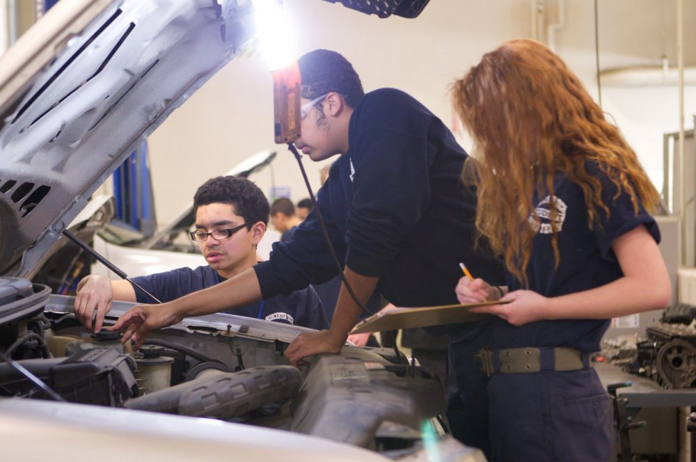 Students work on a car at Worcester Technical High School. (US Department of Education/Flickr)