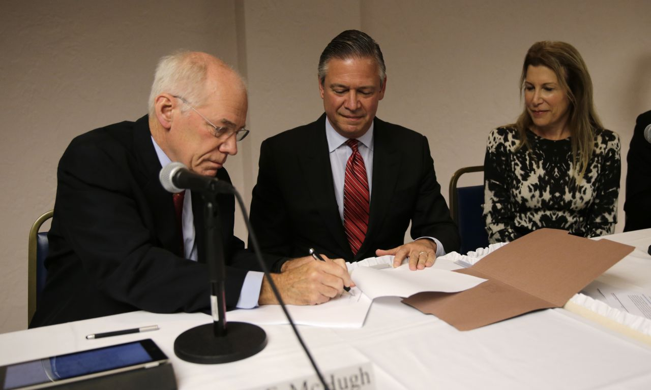 Wynn Senior Vice President Robert DeSalvio, center, looks on as James McHugh, left, signs a licensing agreement in favor of a Wynn casino Wednesday. (Charles Krupa/AP)
