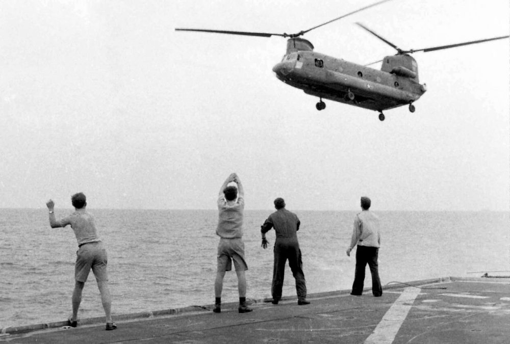 In this April 29, 1975 photo provided by courtesy of American Experience and Hugh Doyle, aboard the USS Kirk, crew members signal the Chinook to hover over the deck and drop its passengers out. (AP)