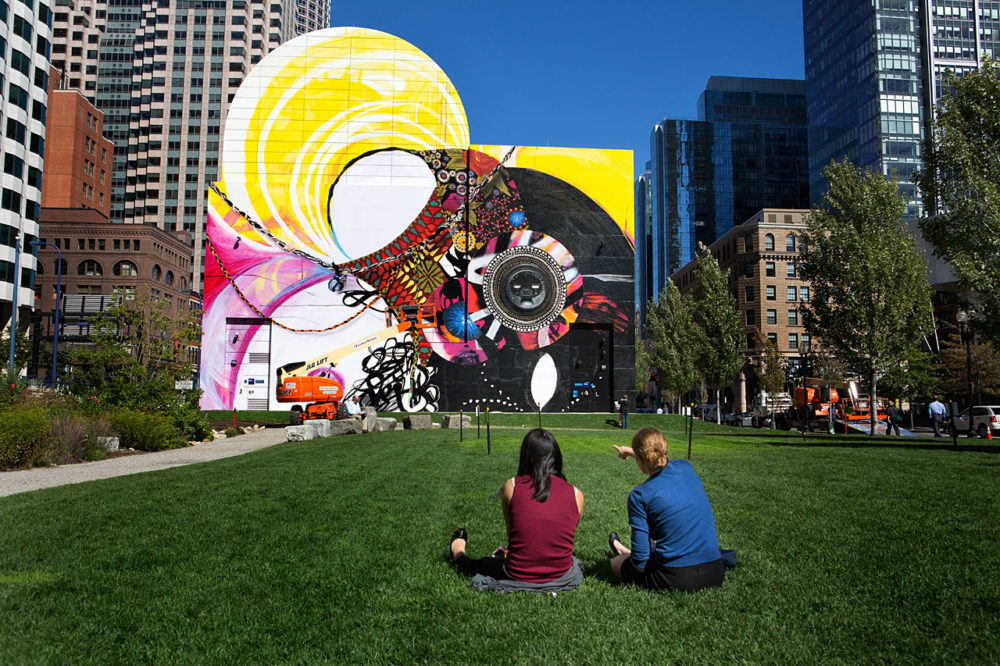 Two women sitting on the grass during a lunch break point out elements of the new mural at Dewey Sq.  (Jesse Costa/WBUR)
