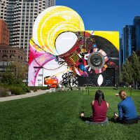 Two women point out elements of the new Dewey Square mural during a lunch break in the park. (Jesse Costa/WBUR)