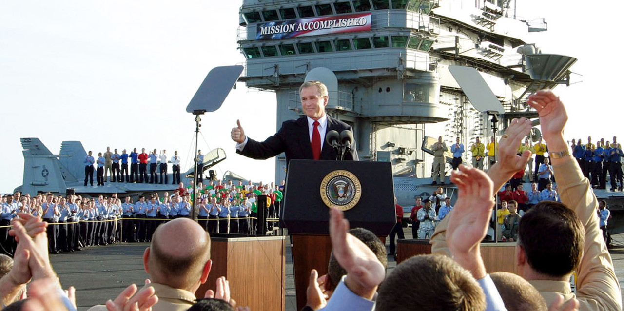 """In this May 1, 2003 file photo, President Bush gives a """"thumbs-up"""" sign after declaring the end of major combat in Iraq as he speaks aboard the aircraft carrier USS Abraham Lincoln off the California coast. We take a look back at the U.S.'s century of involvement in Iraq as the U.S. engages ISIS in Iraq and Syria.  (J. Scott Applewhite/AP)"""