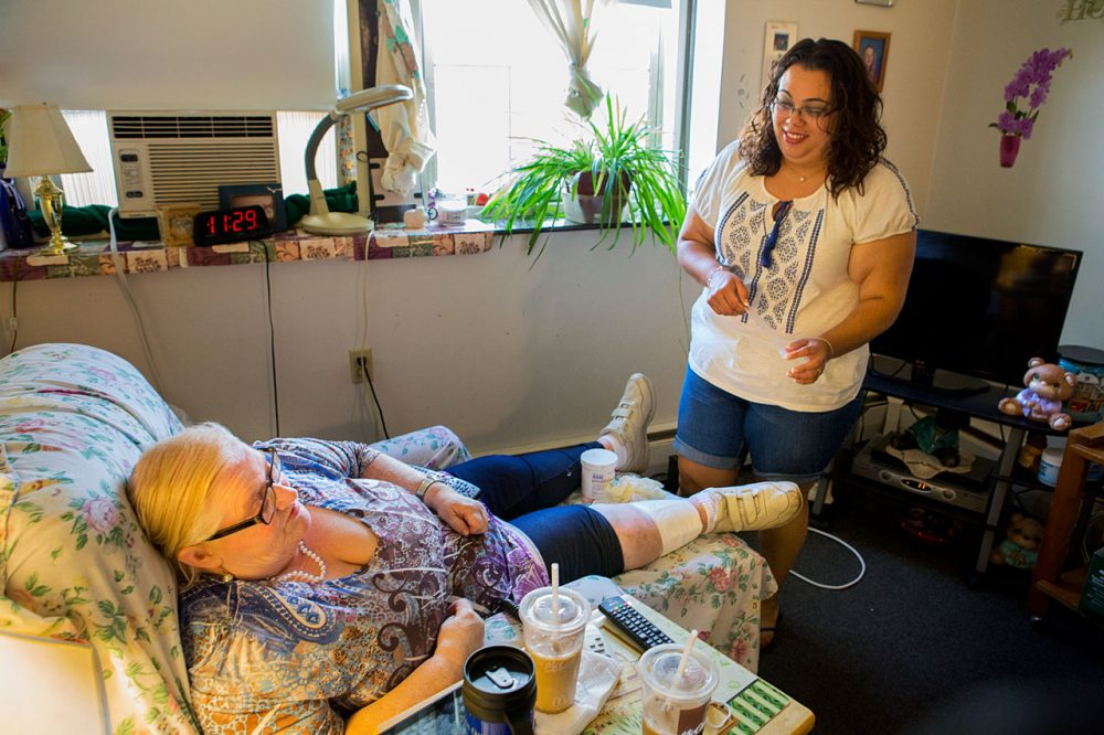 "Rosario Cabrera, right, attends to Donna, her ""consumer,"" in Donna's New Bedford living room. The personal care attendant makes $13.88 an hour, but hopes for benefits like sick time. (Jesse Costa/WBUR)"