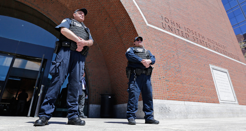Department of Homeland Security police officers stand watch outside the Moakley Federal Courthouse in Boston on May 1, 2013. (Charles Krupa/AP)