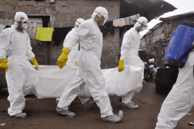 Health workers carry the body of a woman they suspect died from the Ebola virus in Monrovia in 2014. (Abbas Dulleh/AP)