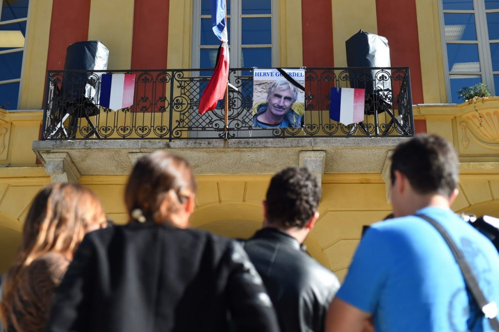 A picture of mountain-guide Herve Gourdel is placed on the town hall's balcony next to the French flag put at half-mast on September 25, 2014, in Saint-Martin-Vésubie, following Gourdel's beheading by Jihadists linked to the Islamic State group in Algeria. )(Anne-Christine Poujoulat/AFP/Getty Images)