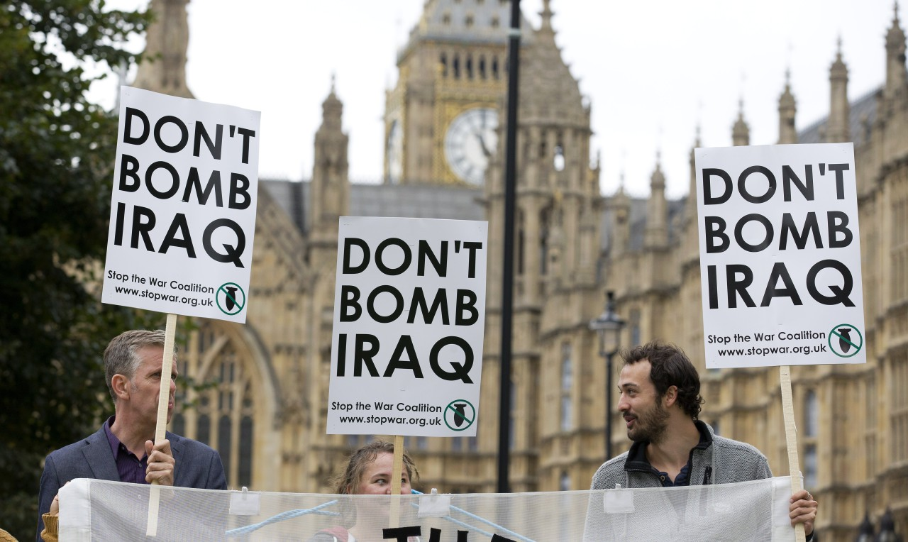 """Protesters hold placards which read """"Don't Bomb Iraq"""" outside the Houses of Parliament where lawmakers are expected to vote in favour of joining air strikes against Islamic State (IS) militants in central London on 26 September, 2014. (Justin Tallis/ AFP)"""