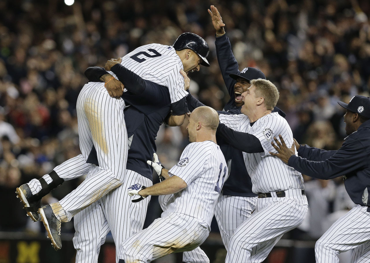 New York Yankees' Derek Jeter (2) is mobbed by teammates after driving in the winning run with a single against the Baltimore Orioles in the ninth inning of a baseball game Thursday. The Yankees won 6-5. (Julie Jacobson/AP)