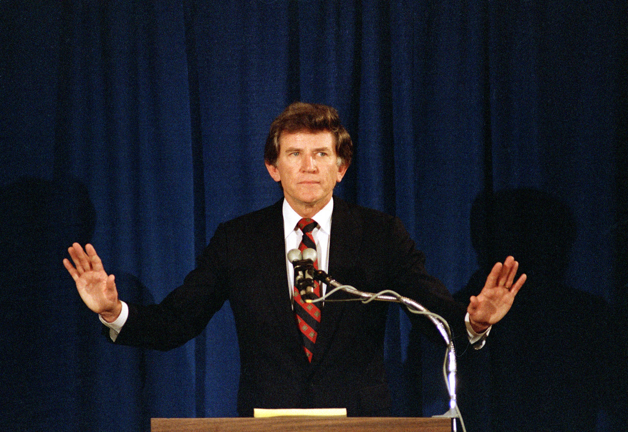 Former U.S. Senator Gary Hart waves his arms to quiet applause from supporters, during a press conference announcing his withdrawal from the Democratic presidential race in 1987. (Jack Smith/AP)