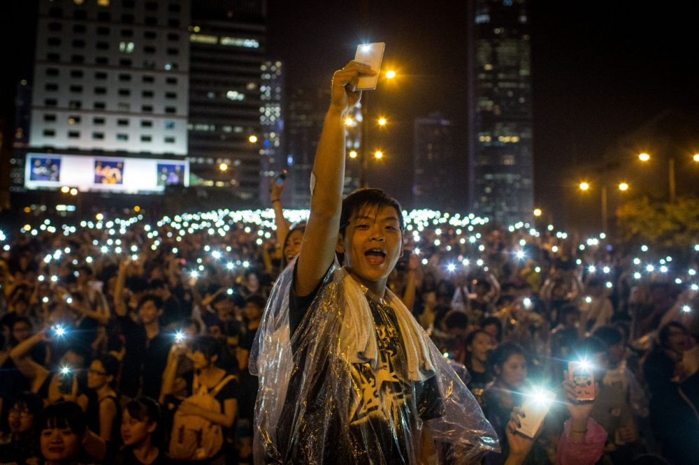 Protesters sing songs and wave their cell phones in the air  outside the Hong Kong Government Complex on September 30, 2014. Thousands of pro democracy supporters continue to occupy the streets surrounding Hong Kong's Financial district despite authorities demanding they withdraw. (Chris McGrath/Getty Images)
