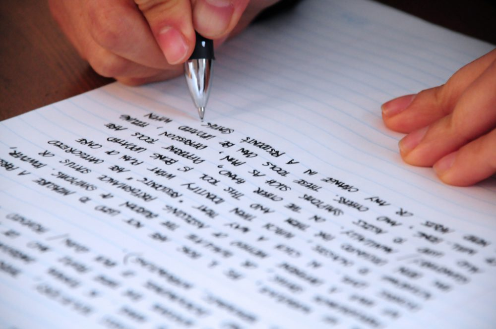 A person that is writing with pen on notebook