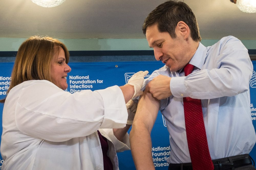 "Dr. Thomas Frieden, director of the Centers for Disease Control and Prevention, receives a flu shot from Sharon Bonadies at the conclusion of a news conference at the National Press Club in Washington, Thursday, Sept. 18, 2014.  ""Vaccination is the single most important step everyone 6 months of age and older can take to protect themselves and their families against influenza,"" said Frieden.  Influenza hospitalized a surprisingly high number of young and middle-aged adults last winter, and this time around the government wants more of them vaccinated. (AP Photo/J. David Ake)"