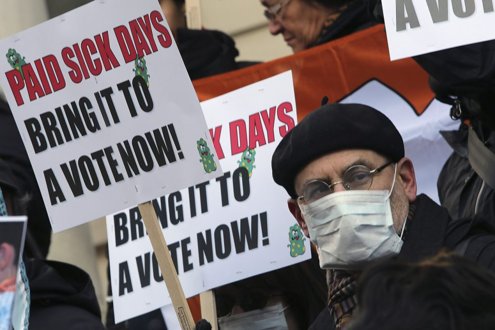 In this Friday, Jan. 18 2013 file photo, activists hold signs during a rally at New York's City Hall to call for immediate action on paid sick days legislation. Two months after a severe flu season forced millions of workers to stay home, paid sick time is becoming an issue for many small business owners. (AP)