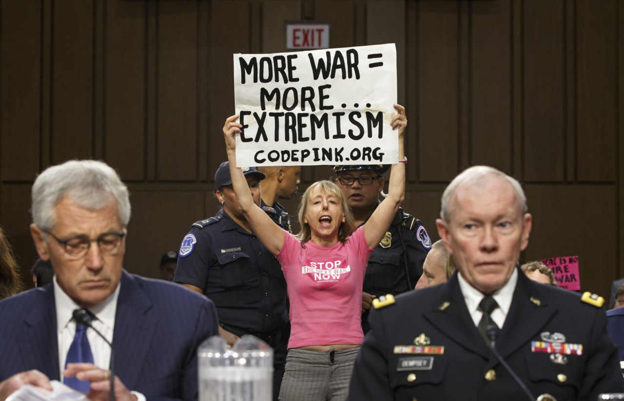 Members of the anti-war activist group CodePink interrupt a Senate Armed Services Committee hearing with Defense Secretary Chuck Hagel, left, and Army Gen. Martin Dempsey, chairman of the Joint Chiefs of Staff, on Capitol Hill in Washington, Tuesday, Sept. 16, 2014. It is the first in a series of high-profile hearings that will measure congressional support for President Barack Obama's strategy to combat Islamic State extremists in Iraq and Syria. (AP)